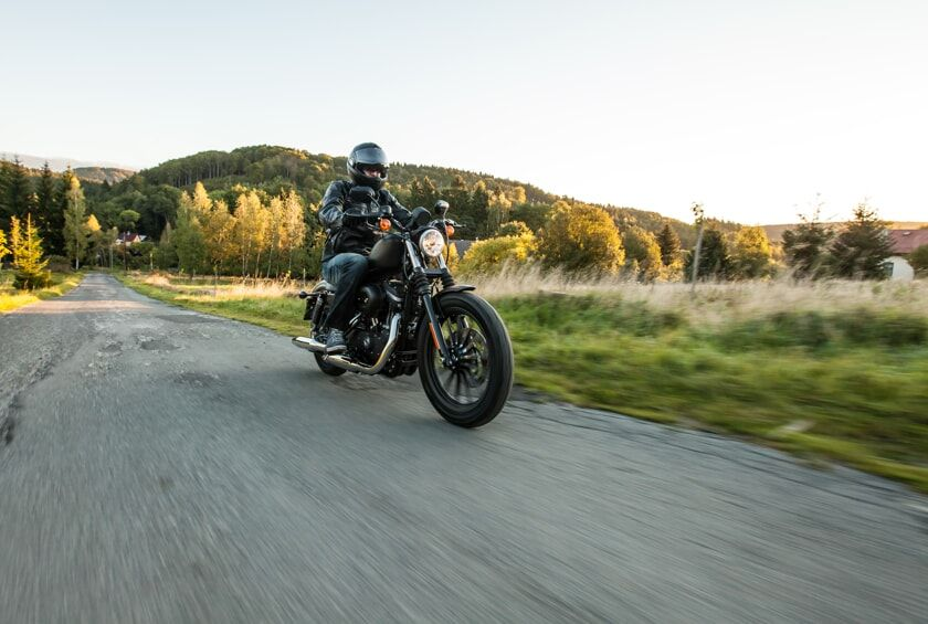 Man riding black motorcycle on country road